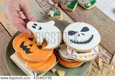 Female Hand Catching A Halloween Themed Buttery Cookie.