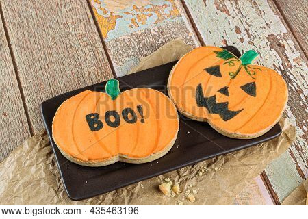 Pumpkin-shaped Buttery Cookies On A Brown Plate.