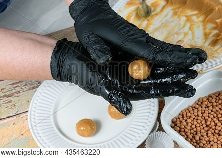 Confectioner With Black Gloves Making Brigadeiro (brigadier) From Dulce De Leche.