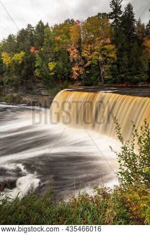 Autumn Photo Of Upper Tahquamenon Falls In Michigan With Water Cascading Into The River Below Surrou