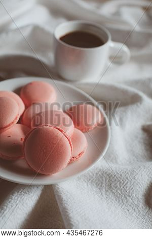 Pink Macaron Cookies With Cup Of Coffee And Rose Flowers On White Background. Spring Still Life Scen