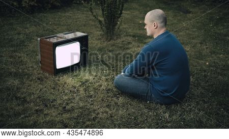 Bald Man Is Sitting On Grass And Looking At Old Retro Tv. There Is Interference On Tv. Concept Of Po