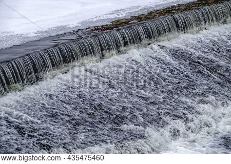 A Small Flat Cascade In A Calm River With Ice In Winter. Water Background