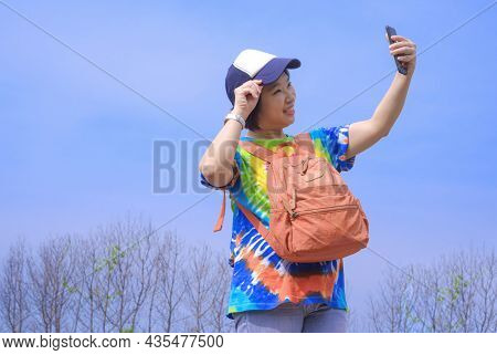 Asian Female Tourist In Colorful Casual Style Smiling Cheerfully And Using Smartphone Taking Selfie