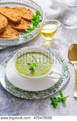 Homemade zucchini soup with tomato ciabatta bread and herbs