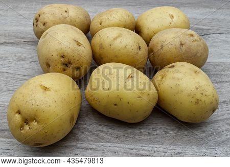 Fresh Potatoes Isolated On Wooden Table. Raw Potato Food.
