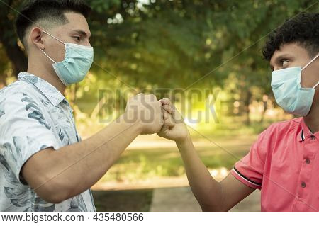 Two Young Men Clashing Their Fists, Image Of Two Young Men Bumping Their Fists In A Friendly Way, Cl