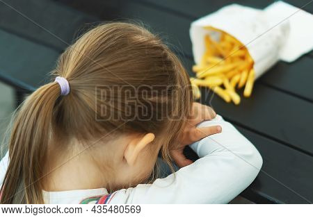 Sad, Moody Girl Doesn't Want To Eat French Fries. Tired Cute Little Girl Tired Of Sitting At A Dark