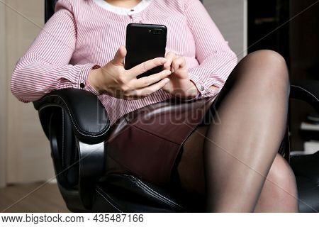 Woman Using Smartphone In Office, Lady In Brown Leather Skirt And Black Lace Stockings Sitting In Ch