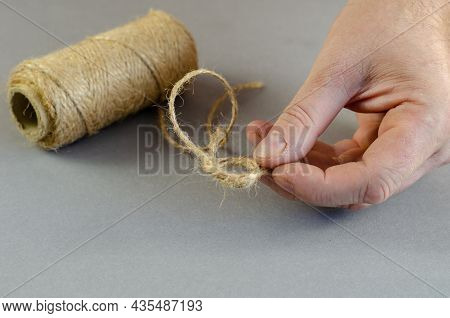 An Adult Man Shows A Knot Of Twine On A Gray Background. His Hand Is Holding A Thin Twisted Thread O