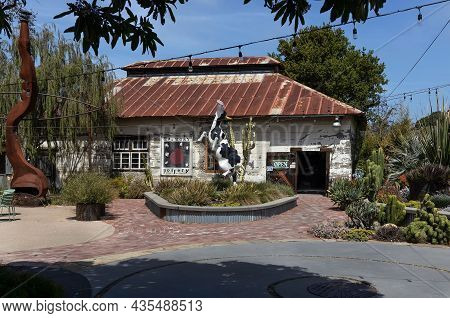 Harmony,california - April 12, 2021: Old Pottery And Garden With Statue Cow In Tiny Historic Town Ha