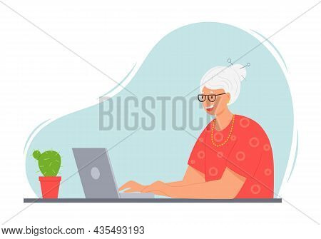 A Happy Elderly Woman With Gray Hair Is Sitting At A Table With A Laptop. An Adult Modern Gradma In