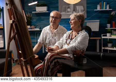 Senior Couple With Artistic Hobby Working On Masterpiece For Art Project In Artwork Room. Elder Man
