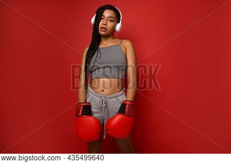 Exhausted Young Athlete Woman Boxer, Sportswoman Wearing Wireless Headphones, Looks At Camera Posing