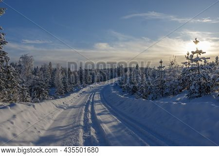 Beatiful Scenery Of Snow Covered Forest Road With Blue Skies And Light Clouds During Evening When Su
