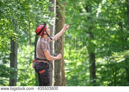 Man Belays His Partner Climber With Belaying Device And Rope. Climber's Handsman Holding Equipment F