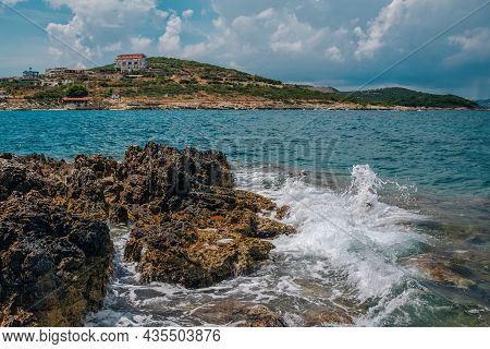 Summer Landscape With Stormy Sea, Rocks And Cliffs, Hills And Small Village On The Horizon, Clouds O
