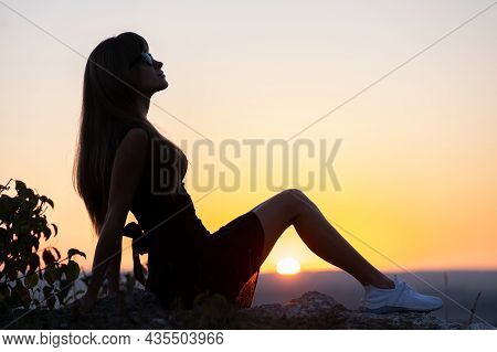 Young Slim Woman In Black Short Dress Sitting On A Rock Relaxing Outdoors At Summer Sunset. Fashiona