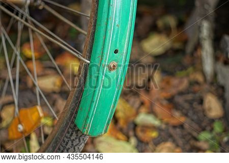 Old Green Metal Bicycle Fender On A Black Bicycle Wheel With Gray Iron Spokes On The Street