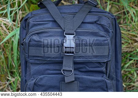 Part Of A Black Tactical Backpack With Harnesses With A Plastic Latch And A Metal Ring On The Street