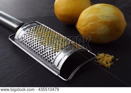 Grater And Fresh Lemons On Black Table