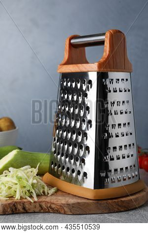 Grater And Fresh Zucchini On Grey Table