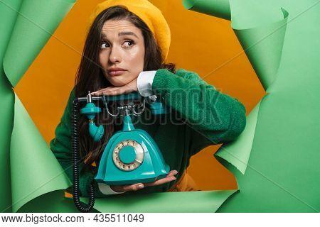 Young sad white woman peeking out hole isolated on green background holding landline phone