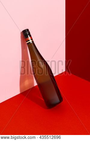 Bottle Of Wine Leaning On The Wall. Alcoholic Drink On Red And Pink Creative Background With Deep Sh