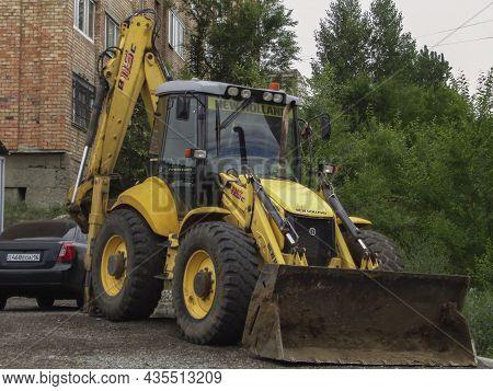 Ust-kamenogorsk, Kz - June 20, 2021.new Holland  Backhoe Loader. Earthwork, Excavation. Smiling Man