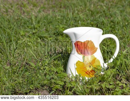 Old White Jug With Pattern Of Poppies On The Green Grass Of The Lawn.  A Ceramic Jug Stands On The G