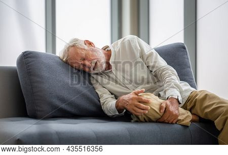 Old Man Suffering From Knee Pain Lying On Sofa In The Living Room, Elderly Man Suffering From Headac