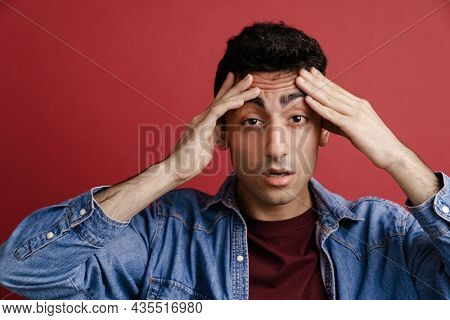 Young middle eastern man with headache holding her head isolated over red background