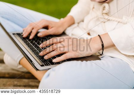 Close up of a young muslim woman in hijab sitting on a bench typing on laptop computer
