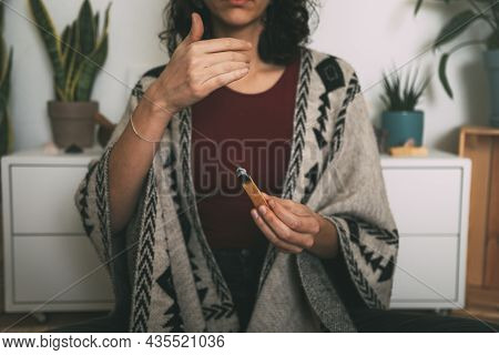 Woman Meditating With A Palo Santo Dressed With A Handmade Poncho.background With Copy Space. Concep
