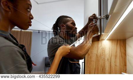Close Portrait Of Professional Carpenter Installing Kitchen Cupboard, Young Female Apprentice Watchi