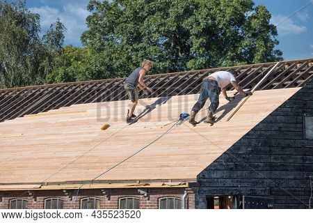 Muiden, The Netherlands - September 08, 2021: Two Builders Busy With Reparing Roof Of Wooden Shed