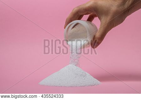 Washing Powder On A Pink Background. Detergent For Washing Clothes. Washing Powder Is Poured Out Of