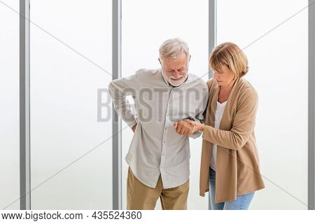 Senior Man Is Having Back Pain And His Attractive Old Woman Supports Him. Elderly Man Suffering From