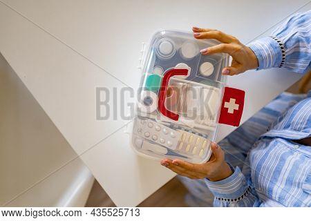 Closeup Female Hand Placing Medicament Domestic First Aid Kit. Storage Organization Emergency Supply