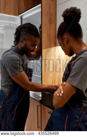Portrait Of Cheerful Handsome African Repair Service Man Near Open Fridge, Searching For Tool In Too