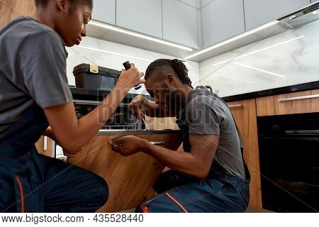 Portrait Diverse Couple Of Professional Repair Persons Looking Into Dishwasher. Skilled African Hand