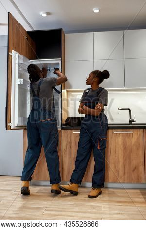 Young Skilled Repairman Troubleshooting Fridge While Young Female Assistant Standing Near With Hands