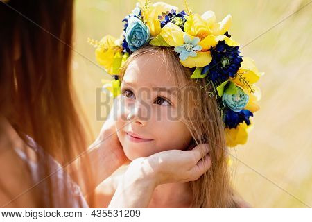 Mother And Daughter In Traditional Ukrainian Wreaths In On Head Blue And Yellow Flag Of Ukraine In F