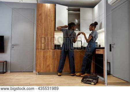 Back View African American Man And Woman, Repair Service Workers, Fixing Cupboard In Modern Kitchen.