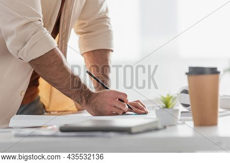 Partial View Of Designer With Pencil Near Blueprint, Blurred Paper Cup And Notebook