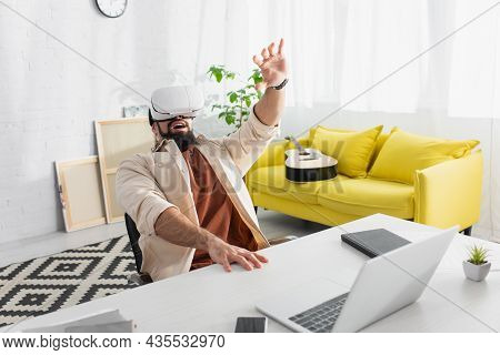 Astonished Latin Freelancer With Outstretched Hand Gaming In Vr Headset At Work Desk