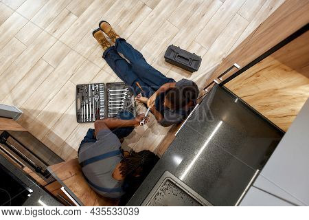 High Angle Photo Of Two Plumbers, Man And Woman In Overalls, Sitting On Floor Trying To Fix Water Le