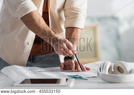 Partial View Of Designer Drawing On Blueprint Near Blurred Digital Tablet And Headphones