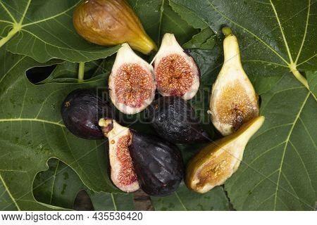 Blue Juicy Figs On Green Fig Leaves.