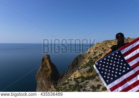 Rear View Of A Young Woman Holding An American Flag Waving At The Coastline Against The Sunny Bright